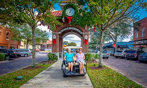 Couple riding in golf cart through downtown Winter Garden